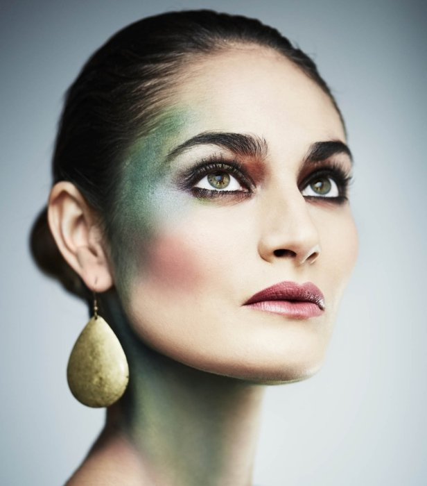A beauty shot of a woman wearing bold and green makeup