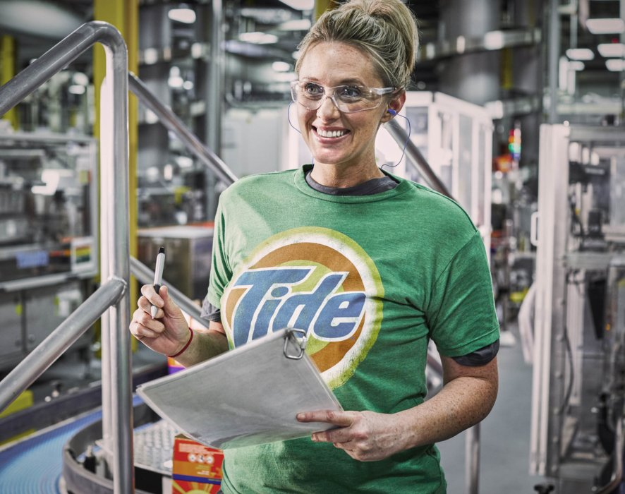 A young happy woman working at the Tide factory