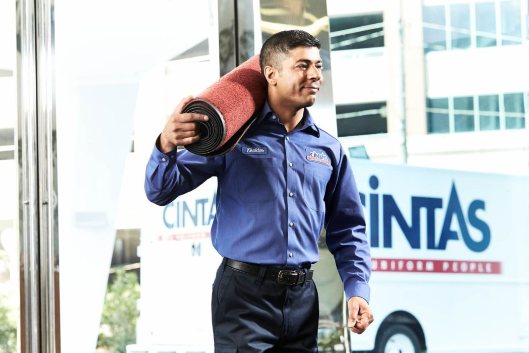 A cintas worker bringing in new floor mats