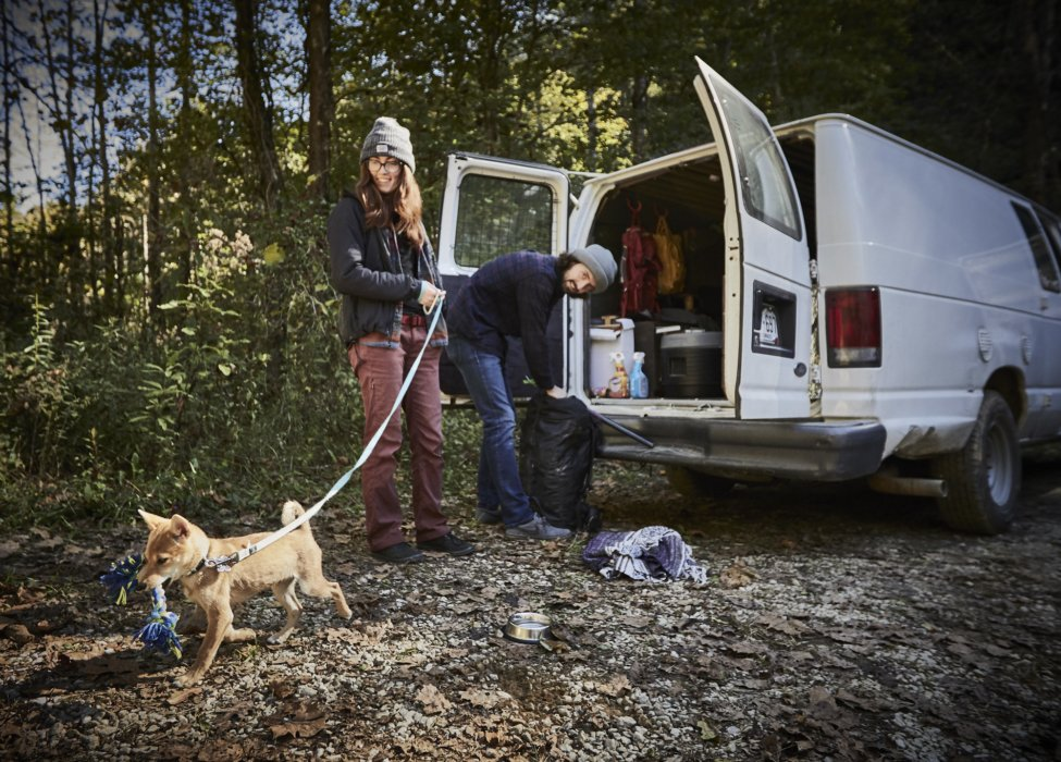 Lifestyle of a couple who lives in a van preparing for a rock climb with a dog - lifestyle photography