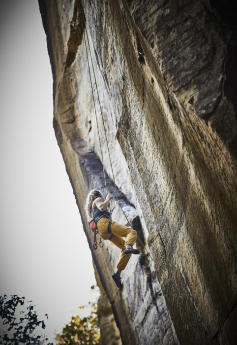 A woman rock climber up on a rock face with ropes