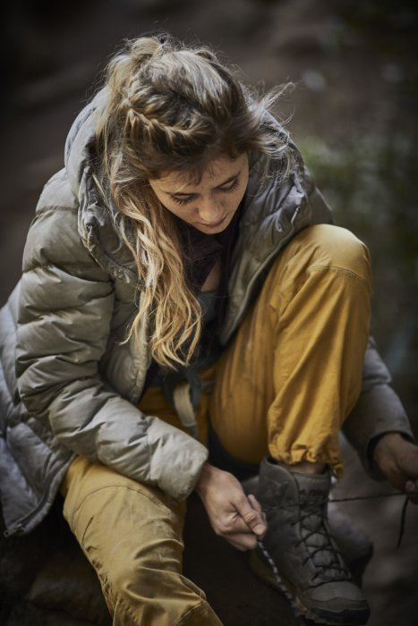 A woman rock climber getting on her boots