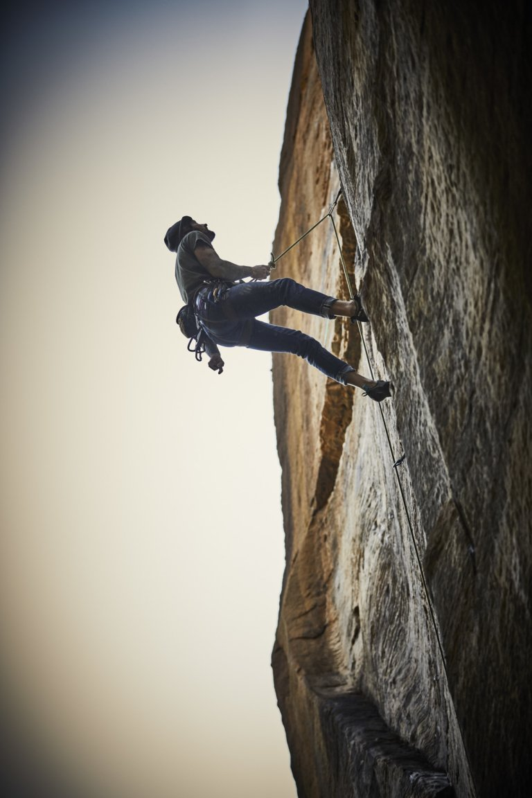 A side view of a male rock climber high on a rock face