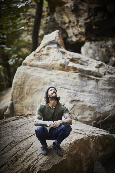 A male rock climber squatting on rocks looking up a rock climb
