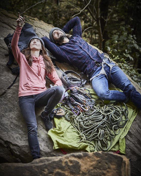 A rock climbing couple taking a break on the rocks with their gear