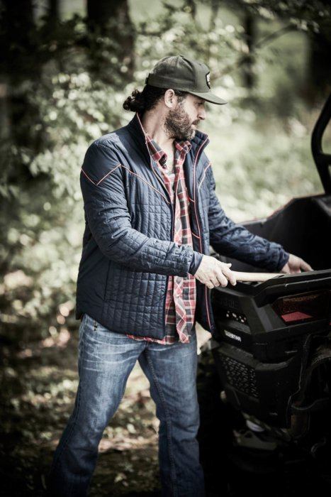 A man wearing rural cloth apparel getting an axe out of his truck