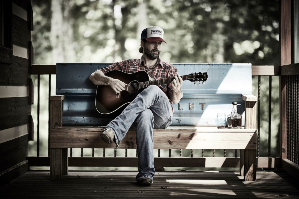A man wearing rural cloth apparel playing guitar on porch