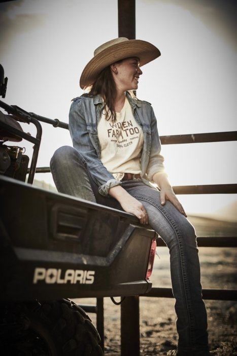 A woman rancher sitting on the back of a 4 wheeler