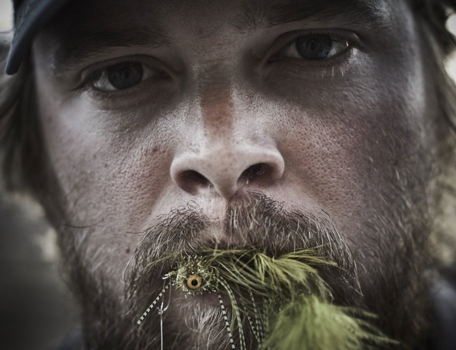 Fly fisherman outdoor with bait being held in his mouth