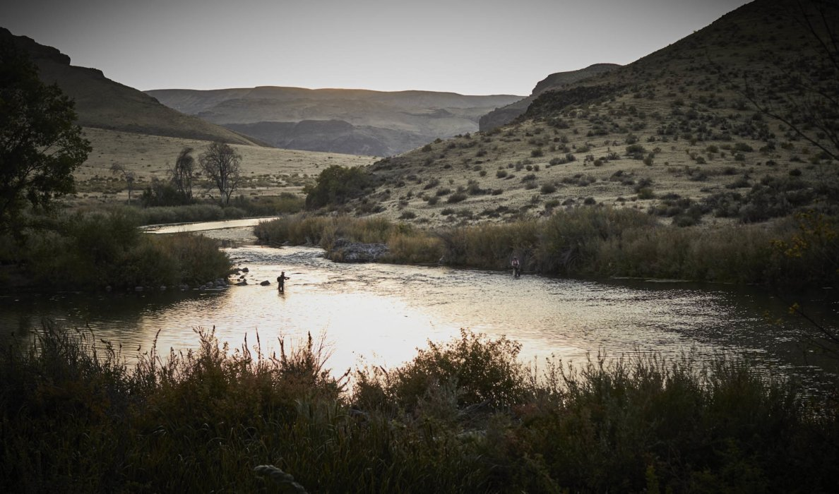 Landscape in Oregon river with fly fisherman in stream