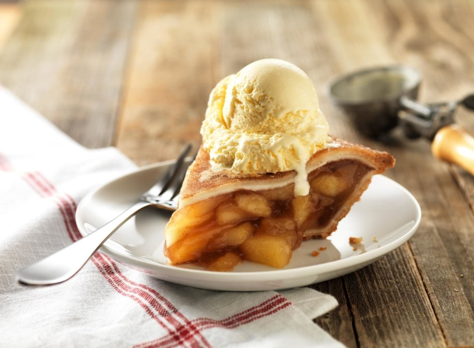 A slice of pie with ice cream on top
