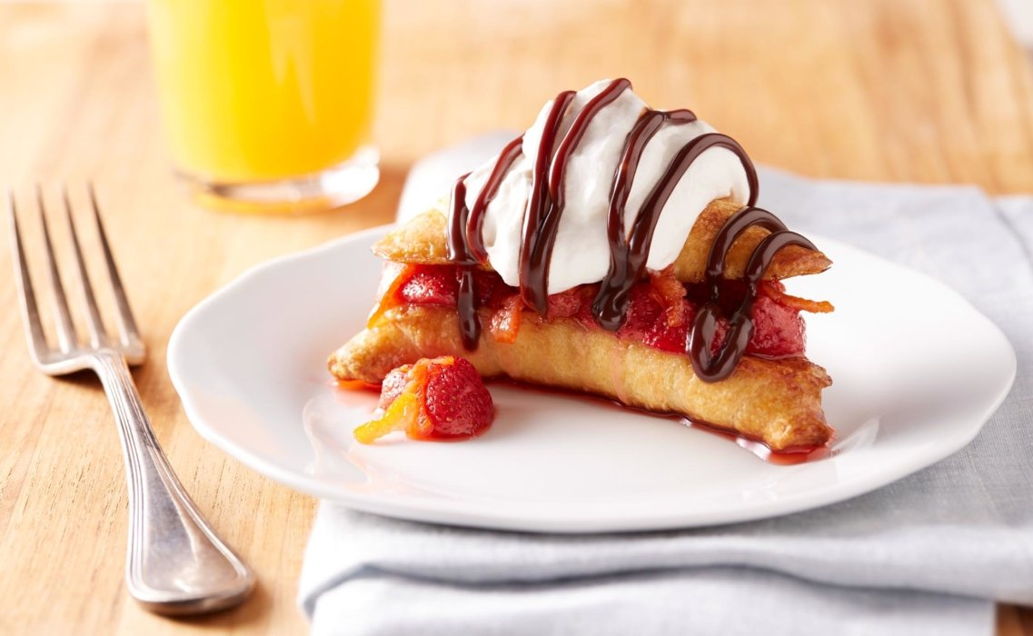 Croissant filled with fruit and topped with whipped cream and syrup
