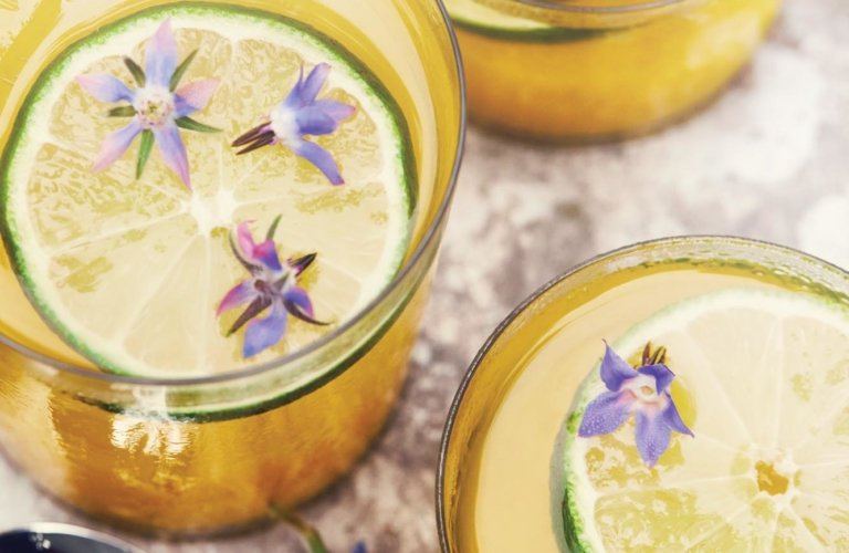 Yellow cocktails with limes and purple flowers