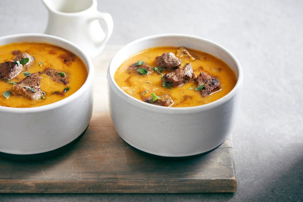 Two bowls of soup with beef