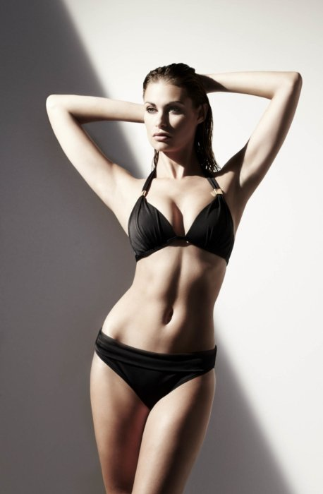 Beauty shot of a woman standing in a black bikini