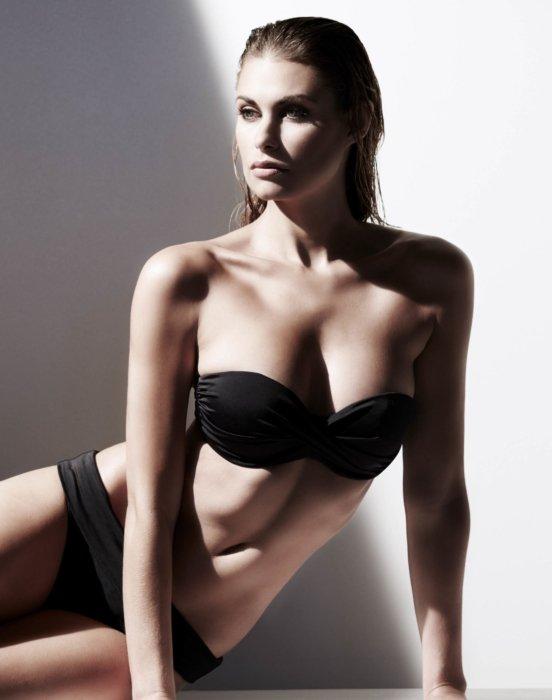 Beauty shot of a woman laying in a black bikini