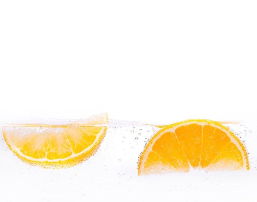 Splashing oranges in water on white background
