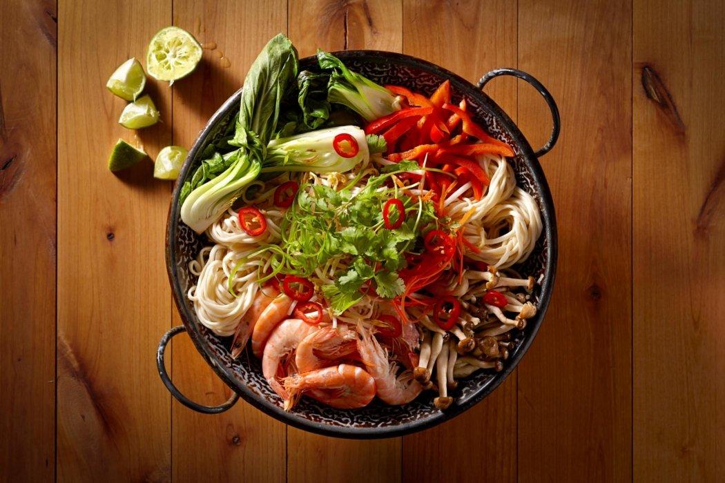 Wok full of raw veggies and shrimp