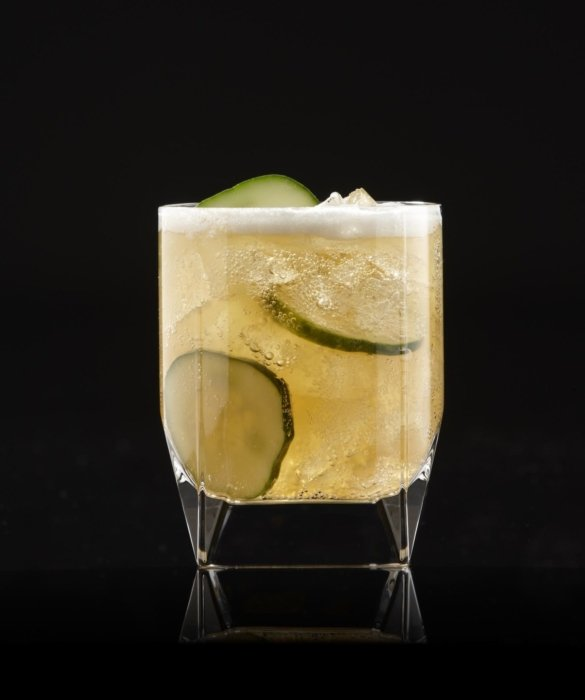 Cucumber cocktail drink in a tumbler with ice on a black background