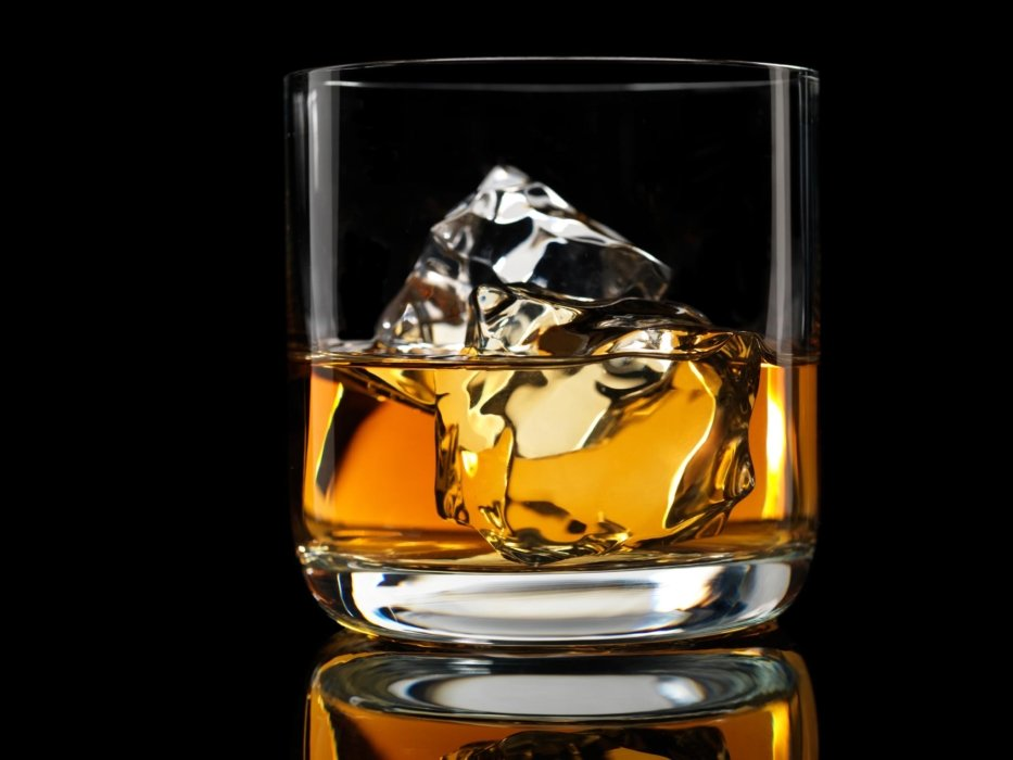 Whiskey with ice in a tumbler glass on a black background