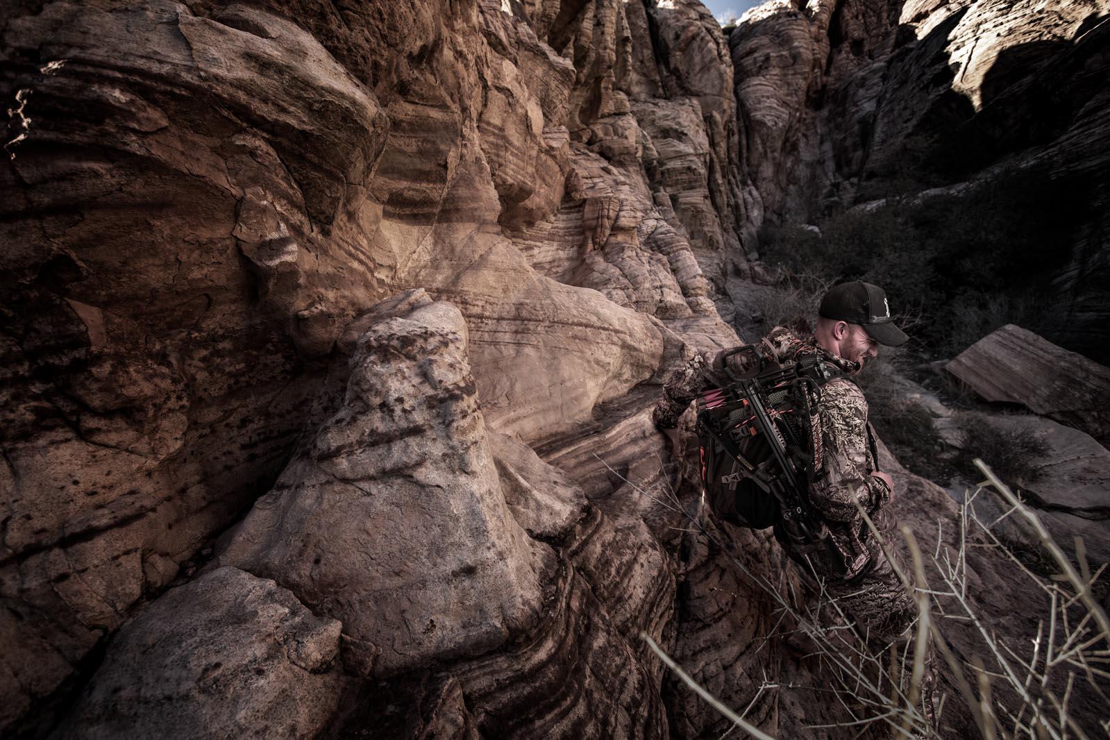 Man wearing gear climbing into a canyon after retouching