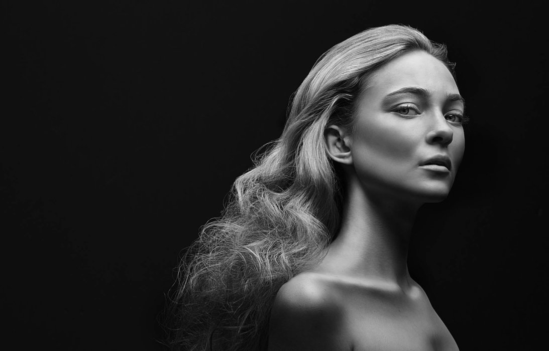 Fashion shoot of a blonde woman on a black background in black and white