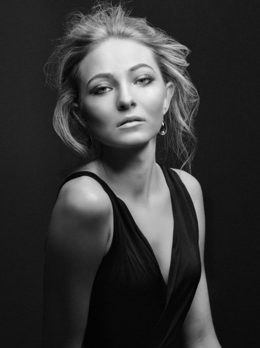 Fashion shoot of a blonde woman wearing a dress on a black background in black and white