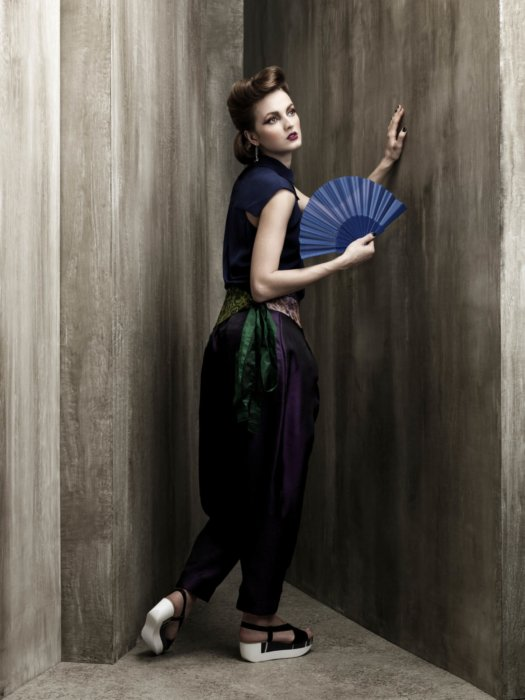Female fashion model wearing navy blue and having a fan