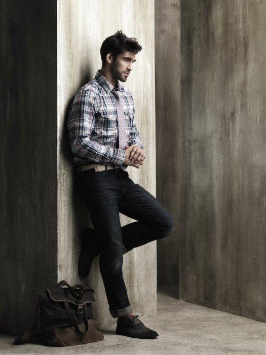 Male fashion model leaning on a wall wearing a shirt and jeans