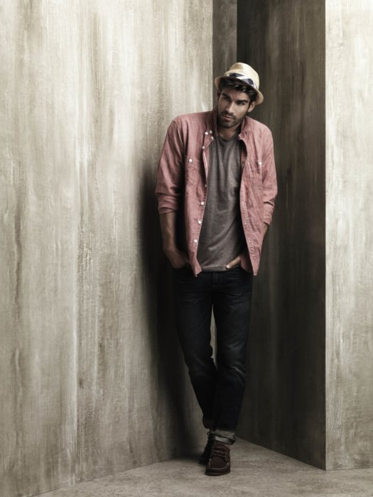Male fashion model leaning on a wall wearing a pink shirt and hat