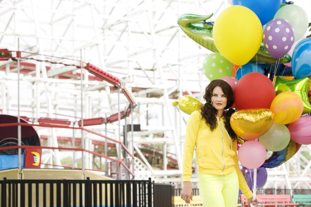 A female fashion model wearing yellow with lots of colors at an amusement park