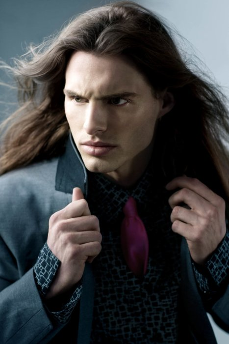 A male fashion model with flowing hair and suit