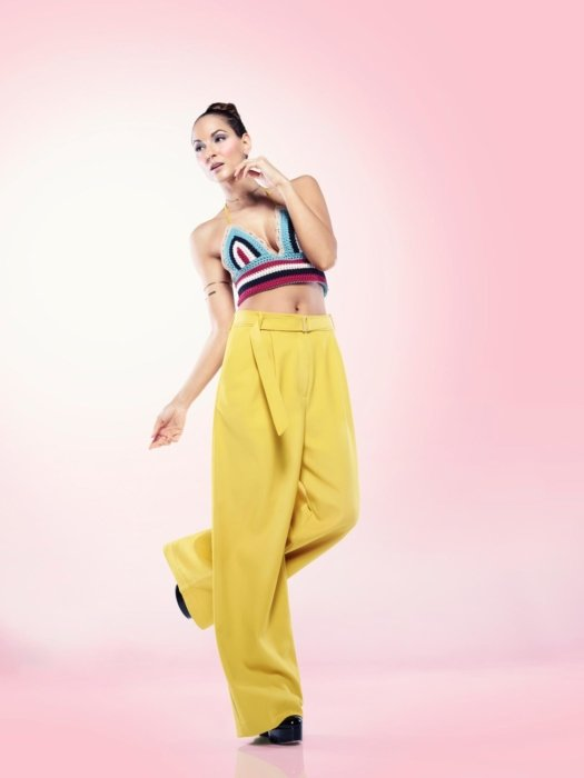 A female fashion model on a pink background with make-up dancing