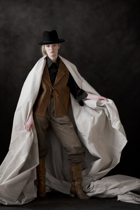 A female fashion model wearing western clothes next to a wooden post