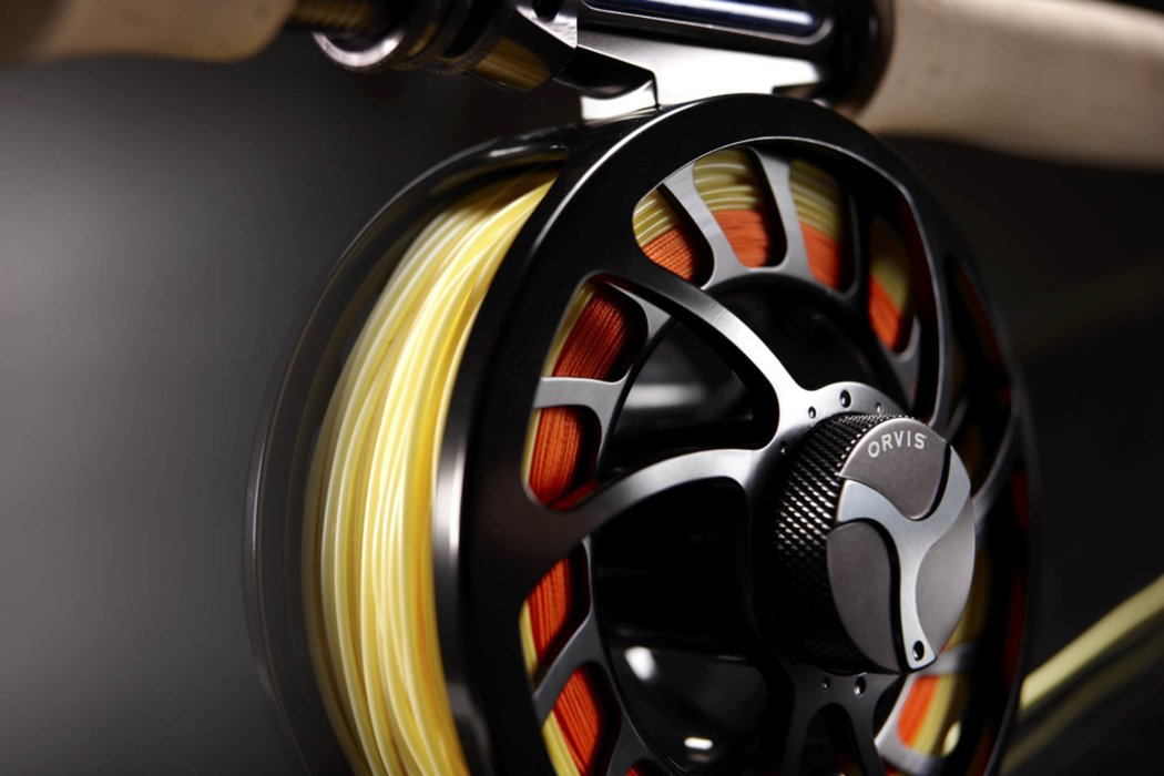 Close up of a fly fishing reel on a black background