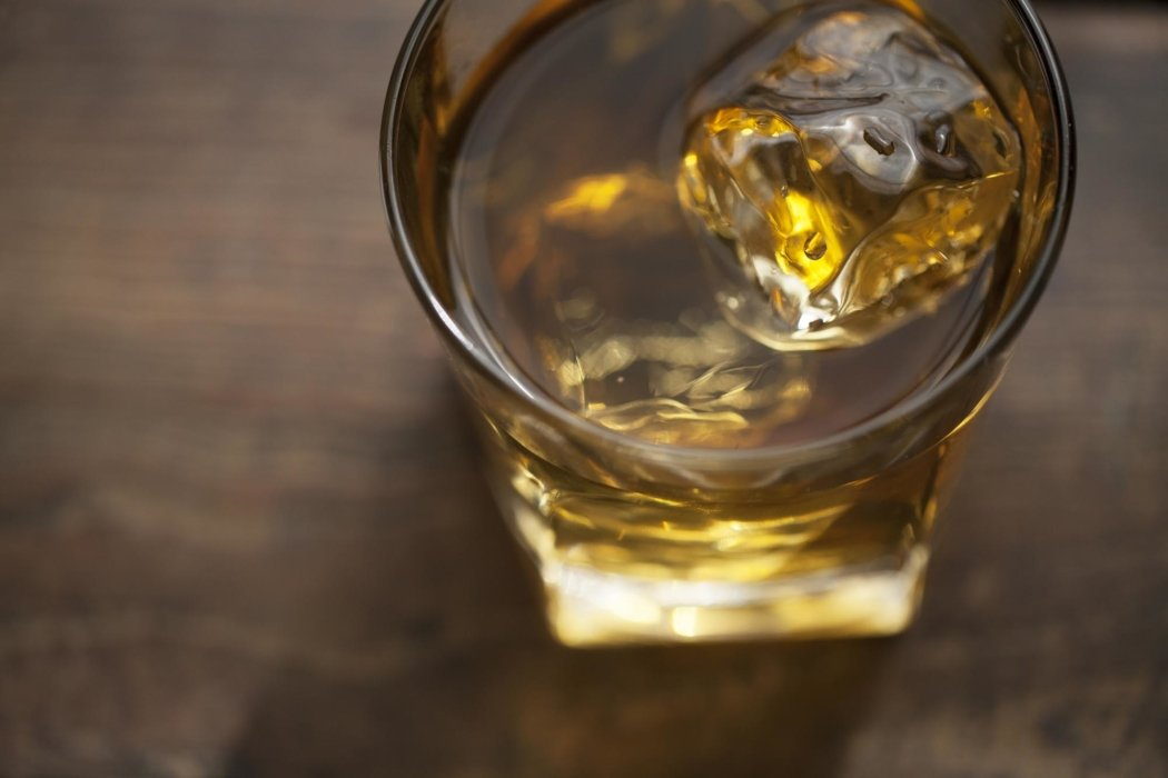 Liquor in ice with a glass on a wood background