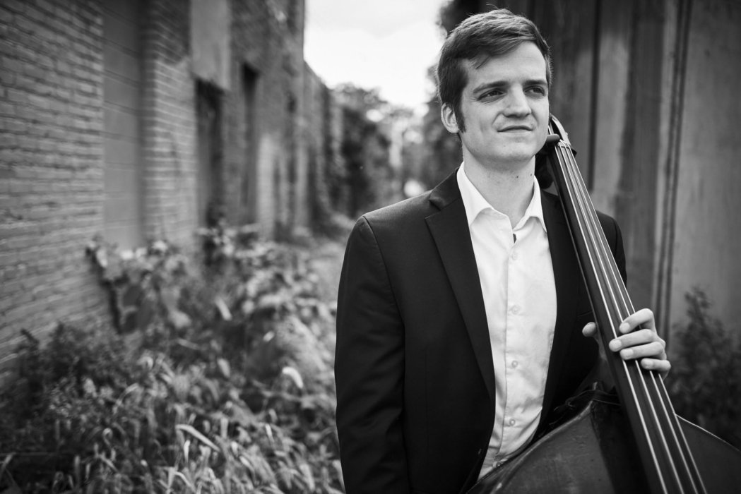 Portrait of a man holding a cello outside