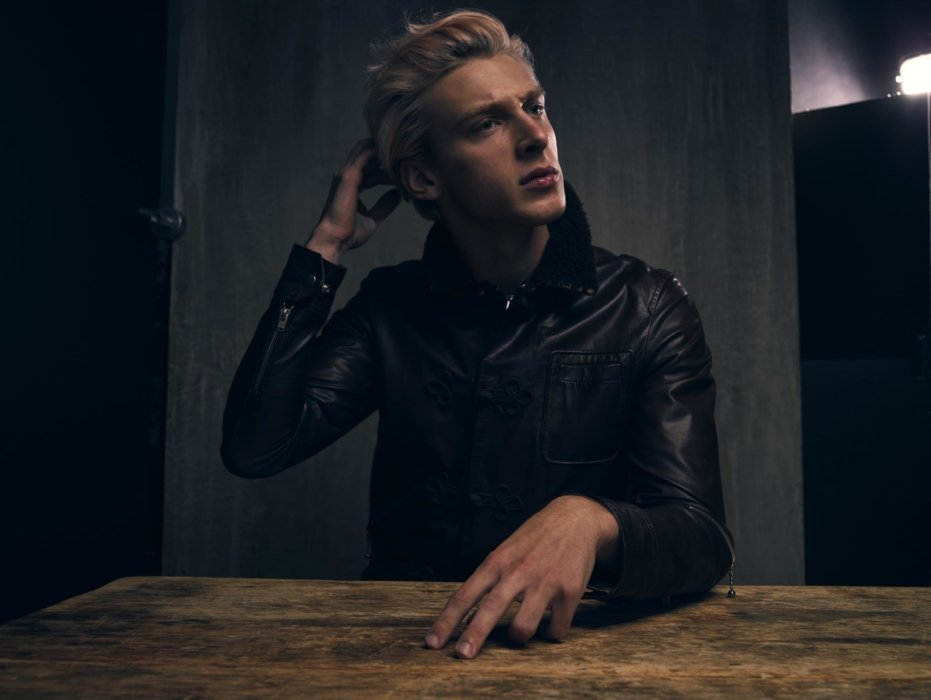 Portrait of a man with blonde hair and leather jacket at a table