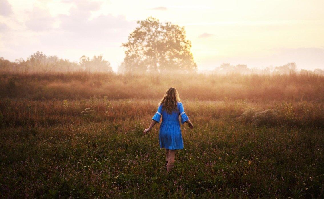 Woman in blue dress walking in a field
