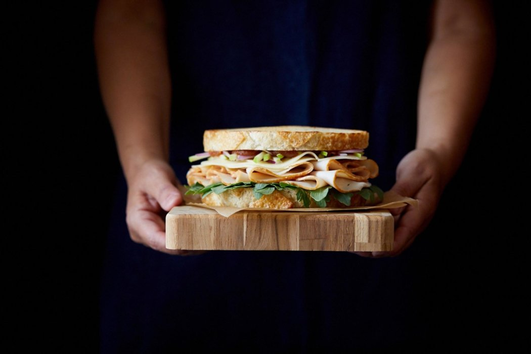 Person holding a deli sandwich on a black background