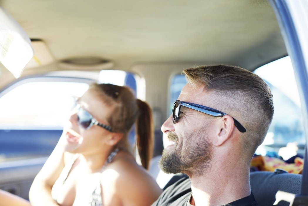 A lifestyle shot of a couple wearing glasses in a car - lifestyle photography