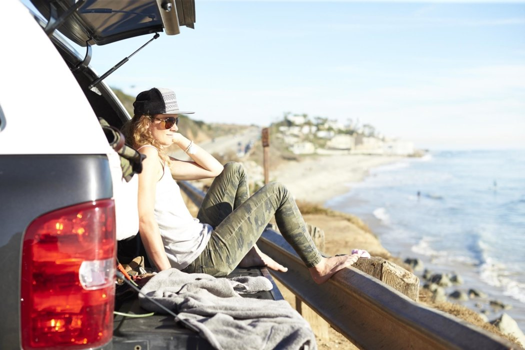 Lifestyle shot of a woman sitting in the trunk of her car at a beach - lifestyle photography