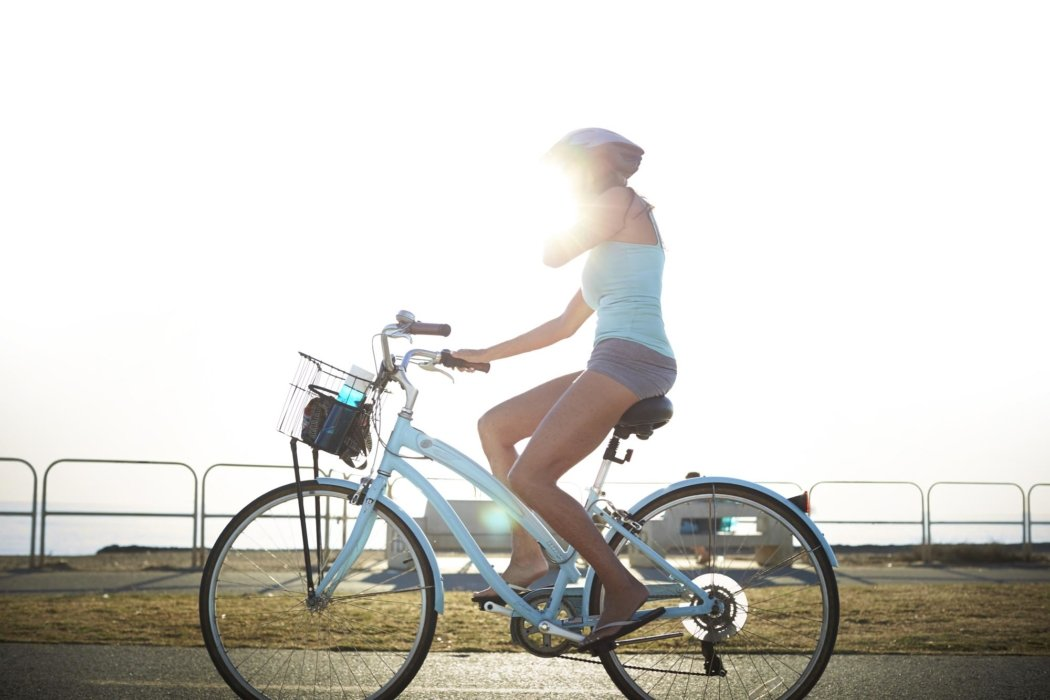 Lifestyle shot of a woman riding a bike at the beach