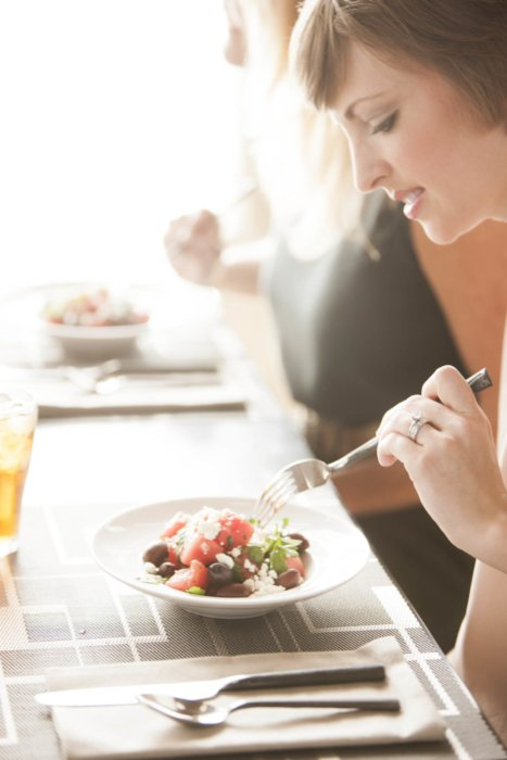 Lifestyle shot of women at dinner eating salads