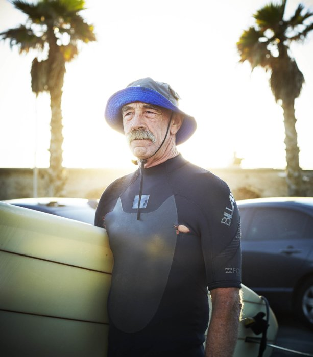 Lifestyle shot of a man getting ready to surf - lifestyle photography
