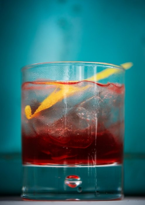 Tiered red and clear cocktail with orange peel in a glass tumbler on a blue background