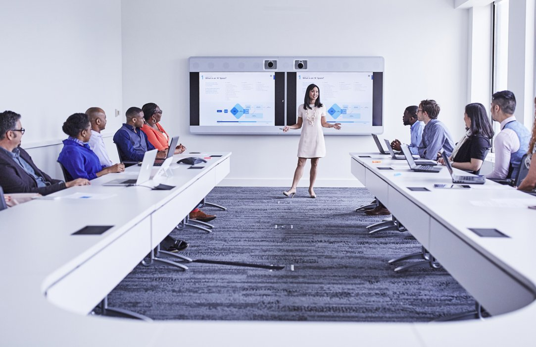 A woman presenting in a board room.