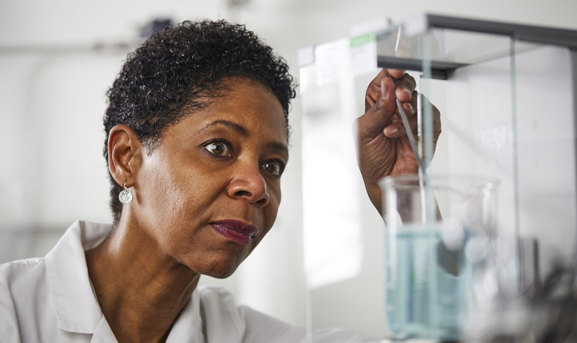 A woman in a lab coat working with a beaker