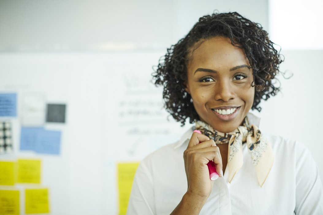 A smiling corporate woman with a idea board behind her