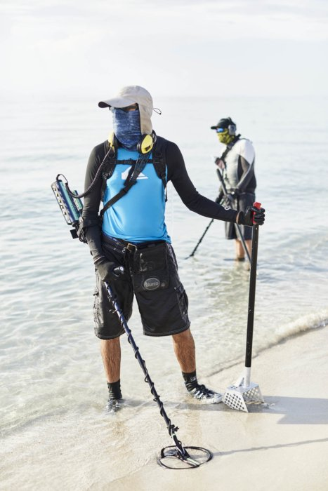 Two people on a beach with metal detectors